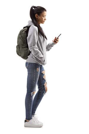 Photo pour Full length profile shot of a young female with a hoodie and ripped jeans holding a mobile phone isolated on white background - image libre de droit