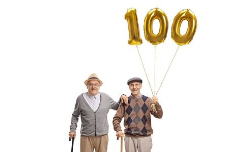 Photo pour Two senior men with a golden number hundred balloon isolated on white background - image libre de droit