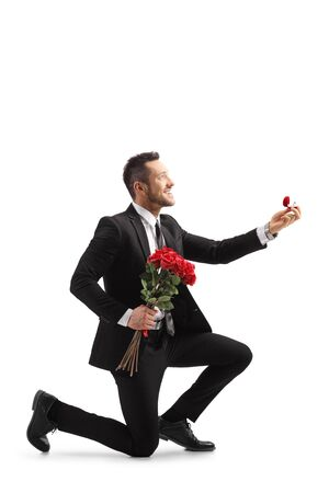 Photo pour Young elegant man in a suit kneeling and holding roses and an engagement ring isolated on white background - image libre de droit