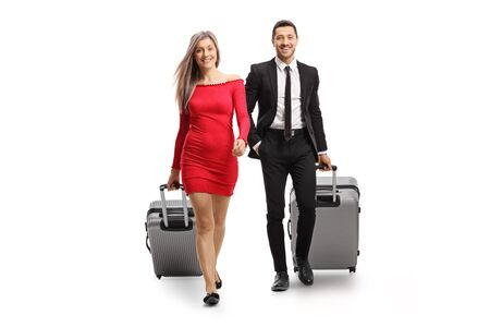 Photo pour Full length portrait of a young woman and man with suitcases walking towards the camera isolated on white background - image libre de droit