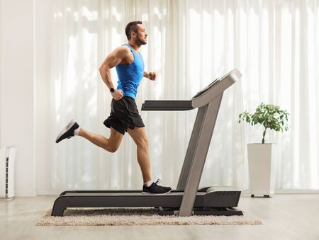 Photo pour Full length profile shot of a young man running on a treadmill at home - image libre de droit