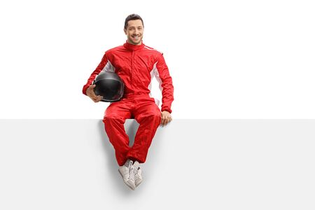 Foto de Full length portrait of a racer in a red uniform sitting on a panel holding a helmet and smiling isolated on white - Imagen libre de derechos