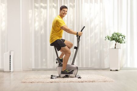 Photo pour Young man exercising on a stationary bike at home - image libre de droit