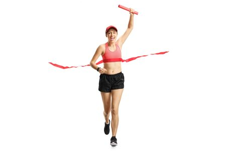 Foto de Full length portrait of a young woman carrying a red baton and finishing a relay race isolated on white - Imagen libre de derechos