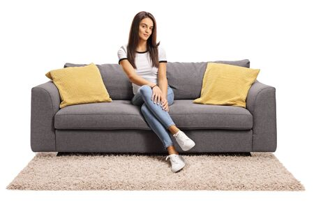 Photo pour Full length portrait of a young female sitting on couch with legs crossed isolated on white background - image libre de droit