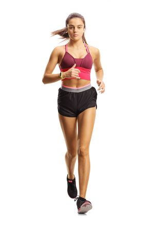 Foto de Full length portrait of a young female athlete running towards camera isolated on white background - Imagen libre de derechos