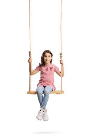 Foto de Full length portrait of a happy little girl sitting on a wooden swing isolated on white - Imagen libre de derechos