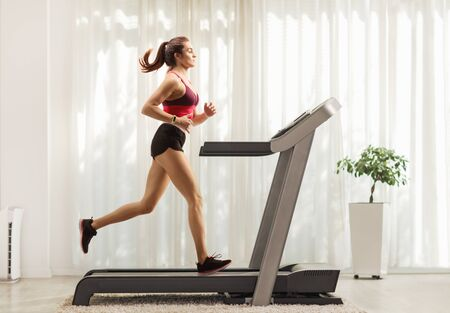 Foto de Full length profile shot of a young woman running on a treadmill at home - Imagen libre de derechos