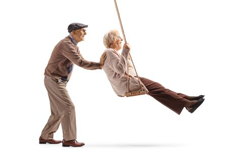 Photo for Full length profile shot of a senior man pushing his wife on a swing isolated on white background - Royalty Free Image