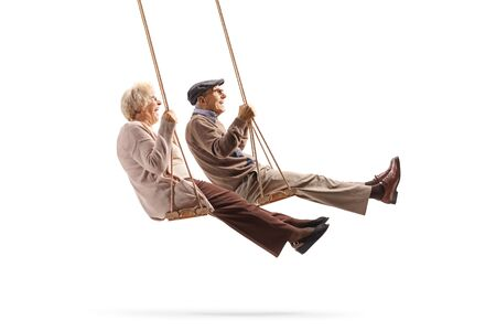 Photo for Full length profile shot of a elderly man and woman swinging on wooden swings isolated on white background - Royalty Free Image
