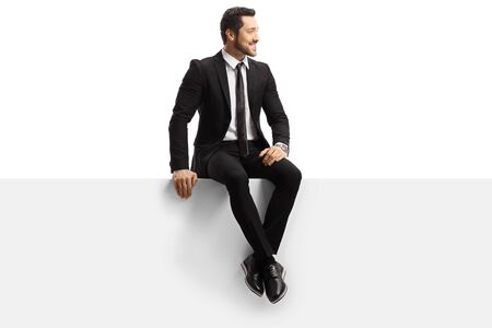 Photo pour Young handsome man in a suit sitting on a panel isolated on white background - image libre de droit