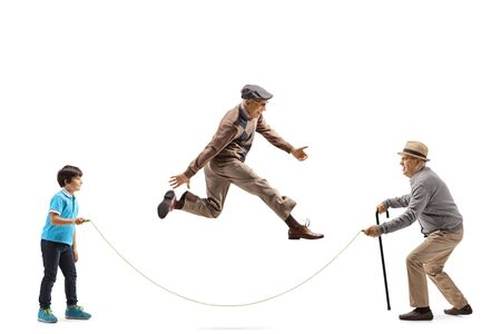 Photo pour Full length profile shot of a grandfather and grandson holding a rope and an elderly man skipping isolated on white background - image libre de droit