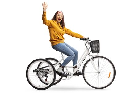 Photo for Cheerful young female riding a tricycle and waving at the camera isolated on white background - Royalty Free Image