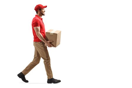 Photo pour Full length profile shot of a delivery man carrying a package and walking isolated on white background - image libre de droit
