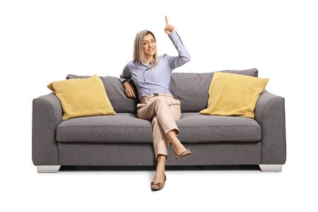 Photo pour Blond woman sitting on a gray sofa and pointing above isolated on white background - image libre de droit