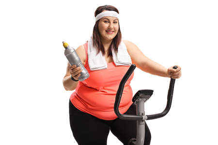 Photo pour Chubby young woman on a stationary bike holding a plastic bottle isolated on white background - image libre de droit