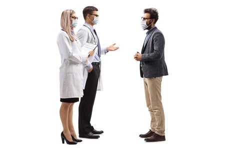 Photo pour Full length profile shot of male and female doctors wearing protective medical masks and talking to a man with a medical face mask isolated on white background - image libre de droit