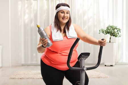 Photo pour Overweight young woman on a stationary bike exercising at home - image libre de droit