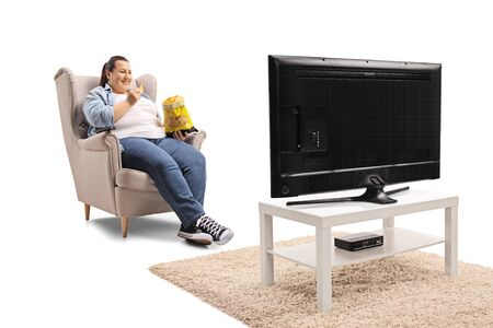 Photo pour Overweight woman watching tv and eating tortilla chips isolated on white background - image libre de droit