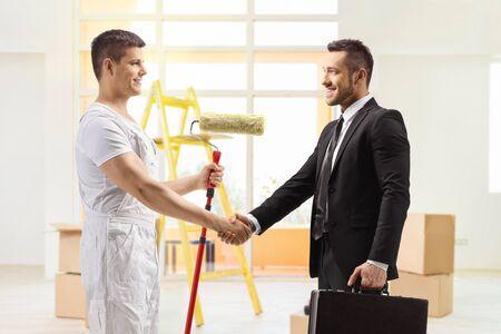 Photo pour Decorator with a paint roller shaking hands with a businessman - image libre de droit