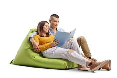 Photo for Young male and female students sitting on a beanbag and reading a book isolated on white background - Royalty Free Image