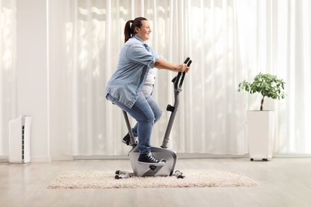 Photo pour Young overweight woman riding an exercise bike at home - image libre de droit