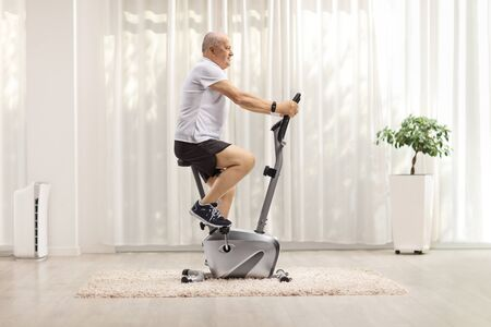 Photo pour Full length shot of a mature man exercising on a stationary bike at home - image libre de droit