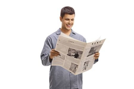 Photo pour Man in pyjamas standing and reading a newspaper isolated on white background - image libre de droit