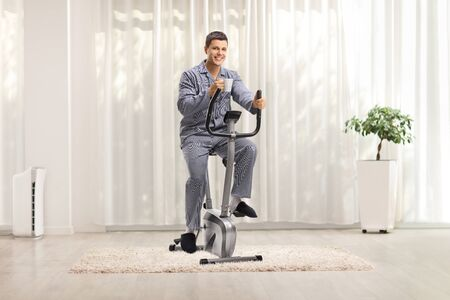 Photo pour Young man in pajamas riding a stationary bike and holding a cup of coffee at home - image libre de droit