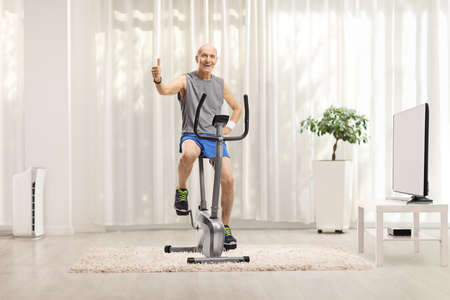Photo pour Cheerful elderly man in sportswear sitting on a stationary bike and gesturing a thumb up sign at home - image libre de droit