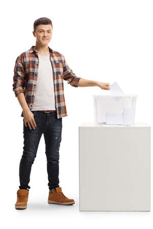 Photo pour Full length portrait of a young man putting a vote in an election box and looking at the camera isolated on white background - image libre de droit