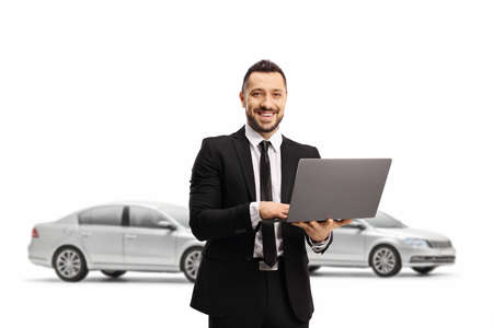 Photo pour Man in a suit with a laptop computer smiling at the camera and posing in front of cars isolated on white background - image libre de droit