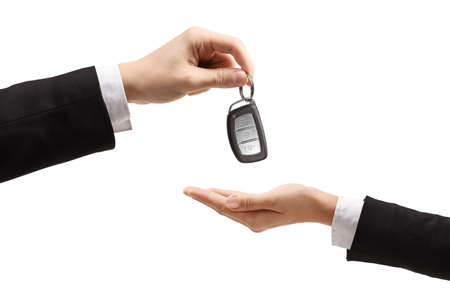 Photo for Male hand giving car keys to a female hand in a formal wear isolated on white background - Royalty Free Image