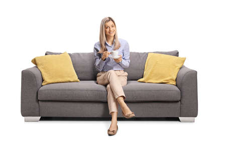 Photo pour Young woman sitting on a couch with a cup of coffee isolated on white background - image libre de droit