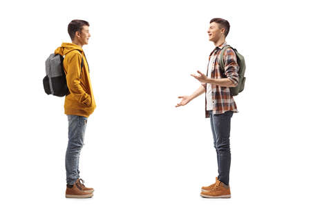 Photo pour Full length profile shot of two male teenage students having a conversation isolated on white background - image libre de droit