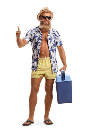 Photo for Full length portrait of a bearded young man in swimming shorts holding a portable fridge and showing thumbs up isolated on white background - Royalty Free Image