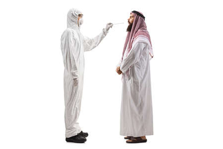 Photo pour Full length profile shot of an epidemiologist in a hazmat suit  taking a cotton swab test from an arab man isolated on white background - image libre de droit