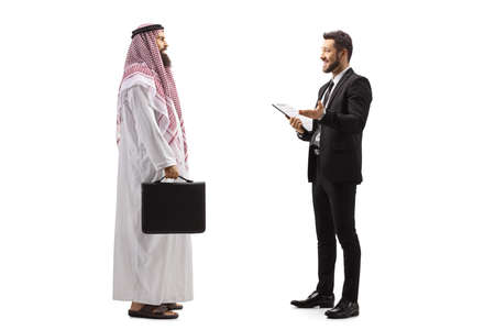 Photo pour Full length profile shot of a businessman talking to an arab man isolated on white background - image libre de droit