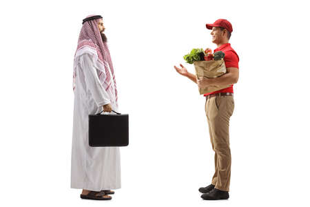 Photo pour Full length profile shot of a courier with a grocery bag talking to an arab man customer isolated on white background - image libre de droit
