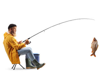 Photo pour Full length profile shot of a young fisherman sitting on a chair and catching fish isolated on white background - image libre de droit