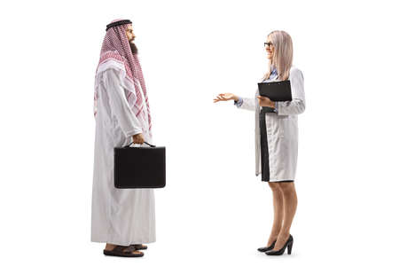 Photo pour Full length profile shot of a female doctor talking to a male arab patient isolated on white background - image libre de droit
