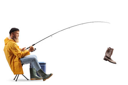 Photo pour Bearded fisherman on a chair catching an old boot with a fishing rod isolated on white background - image libre de droit
