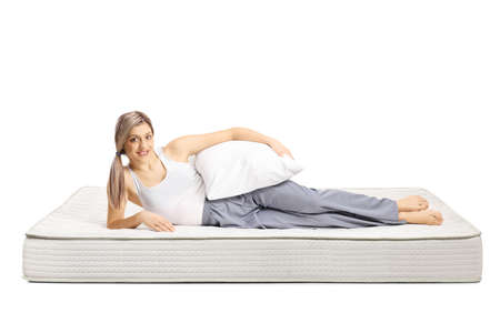Photo pour Young woman lying on a bed mattress in pajamas and holding a pillow isolated on white background - image libre de droit