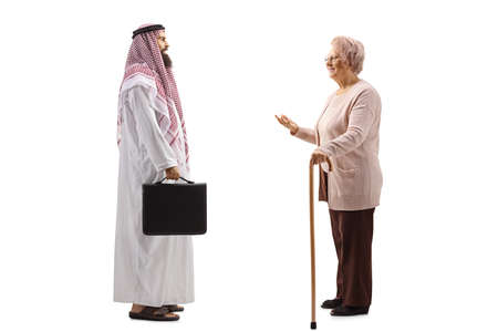 Photo pour Full length profile shot of a senior lady with a cane talking to a saudi arab man isolated on white background - image libre de droit