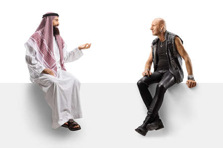 Photo pour Punk and a saudi arab man sitting on a panel and having a conversation isolated on white background - image libre de droit