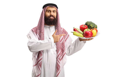 Photo pour Saudi arab man holding a plate of fruits and vegetables and pointing at it isolated on white background - image libre de droit