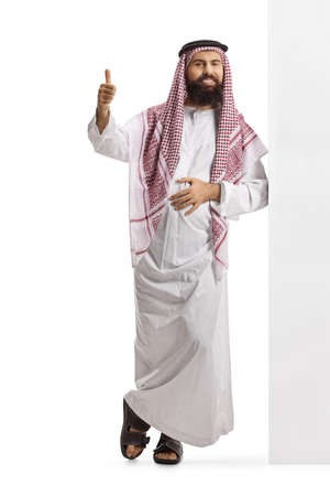 Photo pour Full length portrait of a saudi arab man wearing a traditional thobe, leaning on a wall and gesturing thumbs up isolated on white background - image libre de droit