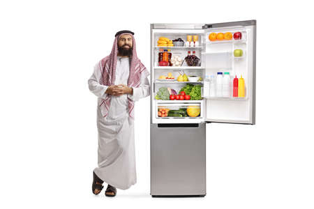 Photo pour Full length portrait of a saudi arab man leaning on a fridge with food isolated on white background - image libre de droit