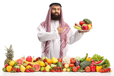 Photo pour Bearded saudi arab man holding a plate with fresh vegetables isolated on white background - image libre de droit