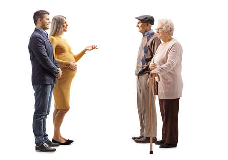 Photo pour Full length profile shot of a young expecting couple talking to an elderly couple isolated on white background - image libre de droit